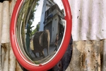 An elephant and mahout, reflected in a mirror, walk through a residential neighbourhood in Bangkok.
