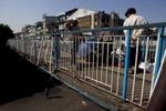 People cross an overpass.
