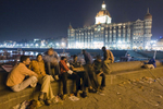 A group of men pass time near the Taj Mahal Hotel in Mumbai.