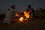 Camel traders keep warm around a fire in Pushkar.