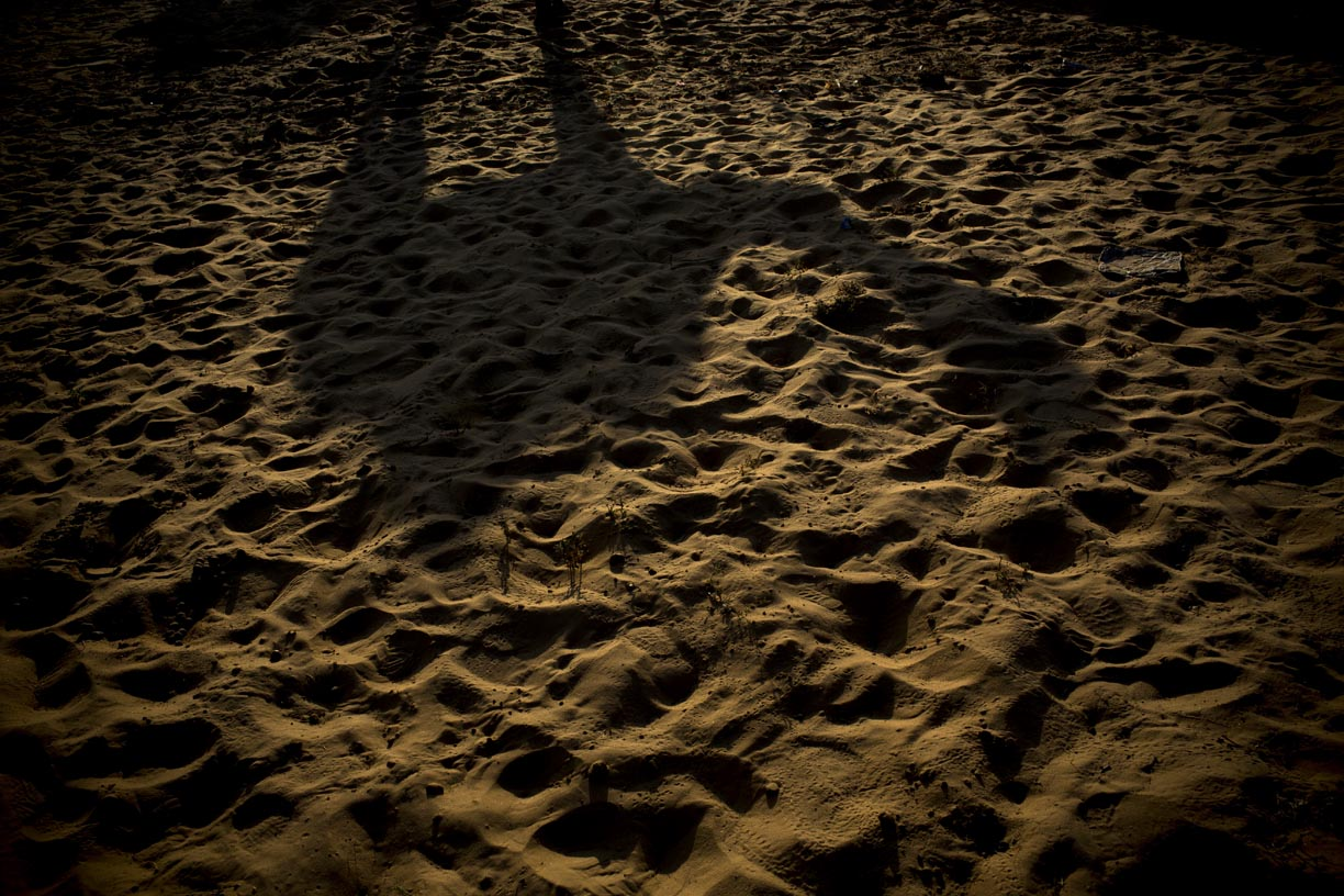 A camel's shadow is cast on the desert sand in Pushkar.