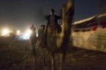 Men ride camels through Pushkar at night.