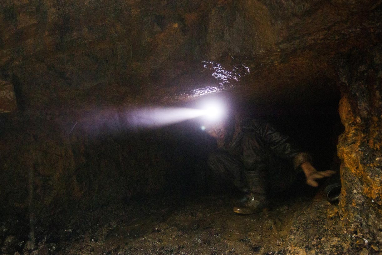 A young man emerges from a rat hole in the Jaintia Hills.