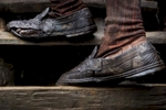 A labourer wearing tattered shoes, walks up from a mining pit in the Jaintia Hills.