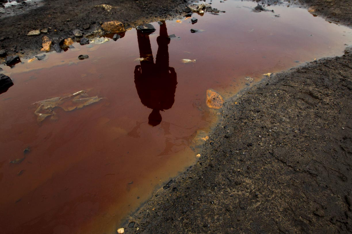 A miner is reflected in contaminated water at a mining site in the Jaintia Hills. Due to its high sulphur content, the coal from the Jaintia Hills is a major pollutant. Coal is commonly dumped on roadways and near bodies of water which has contaminated the water that miners depend on for their sustenance.
