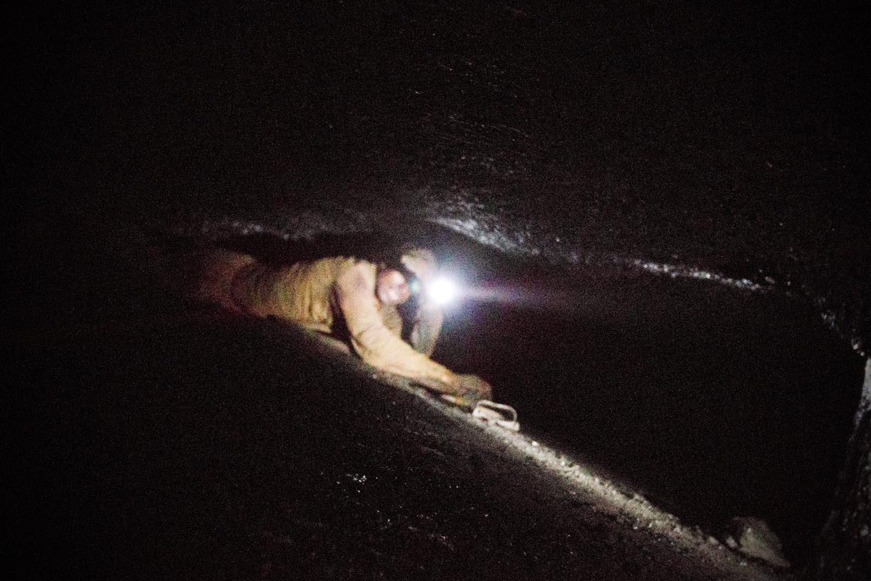 A young miner crawls through a rathole in the Jaintia Hills. Tunnels two feet in height are made into the seam sideways to extract coal. The miners crouch into these tunnels, equipped with only a flash light and a pick-axe to chip away at coal.