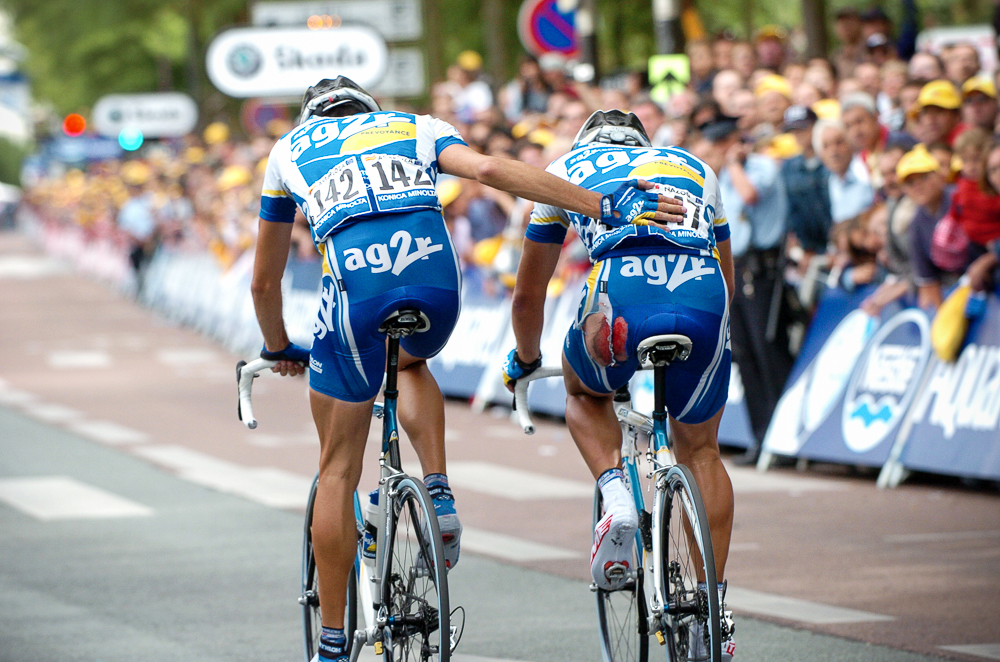 2004 STAGE 6 / Angers, France: Mikel Astarloza ushers his wounded teammate Jean-Patrick Nazon (Team AG2R) towards the finish line on July 9, 2004.
