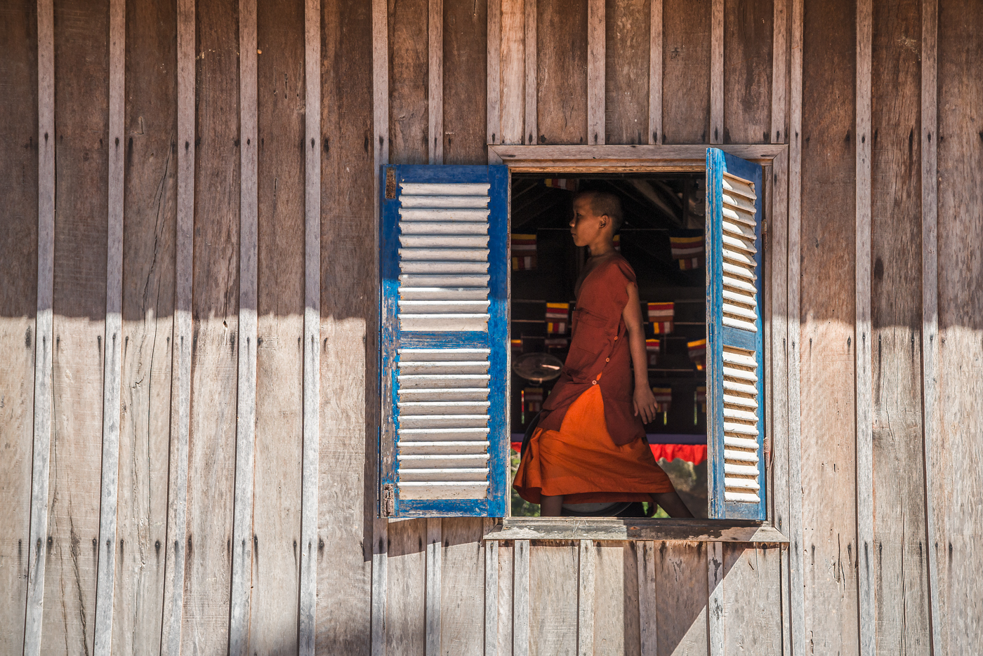 A young monk strides past the window of the monastery where he resides in the remote Cambodian countryside.