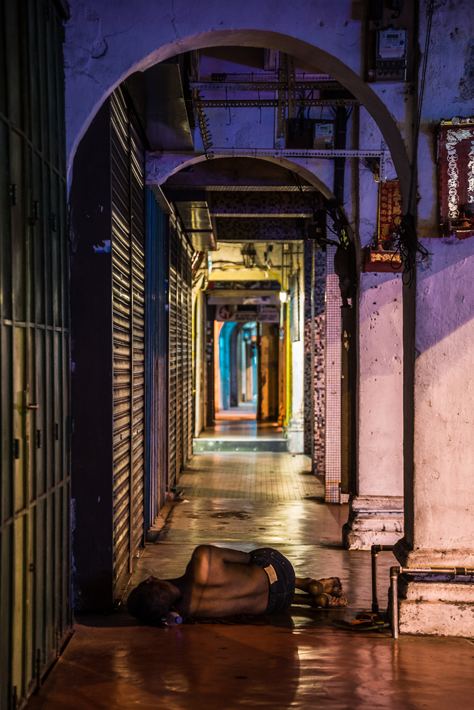 A homeless man finds shelter in a walkway in the Malaysian island-city of Penang.  He rests his head on a water bottle.