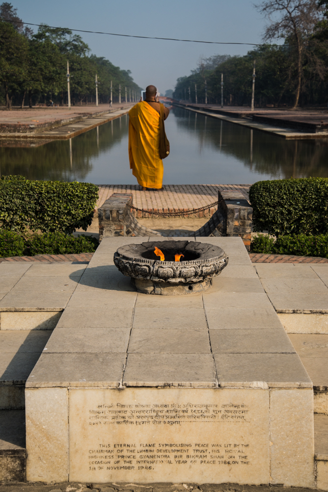 A monk on a pilgrimmage to the birthplace of Bhudda takes a photograph on his tablet.  Behind him burns the Eternal Peace Flame, alight since 1986.