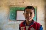 A student poses for a photograph in his classroom in the mountain village of Khalanga.