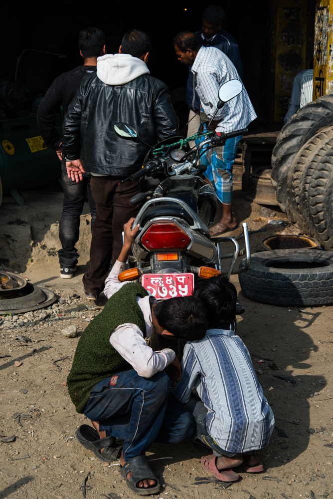 Young mechanics work on a scooter at a tire shop in the hill region of Nepal.