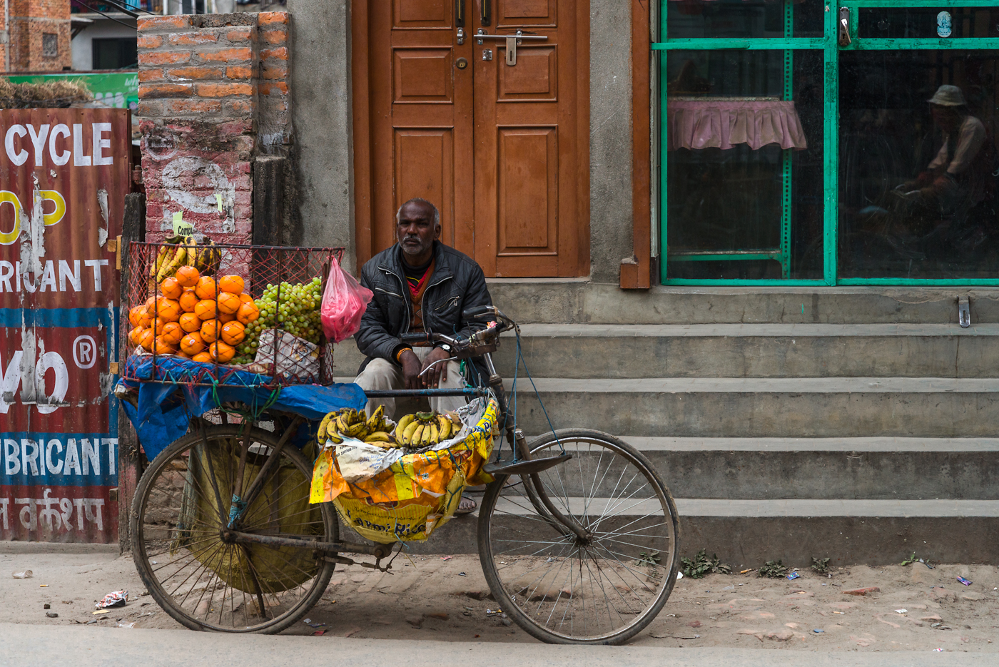 A man rests by his mobile fruit stand on the streets of Kathmandu.