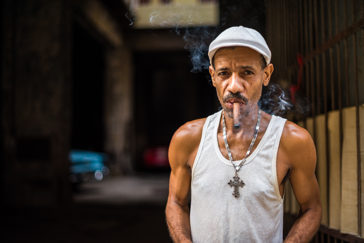 This gentleman was enjoying  a cigar outside of his parking garage.  Taxi drivers in Old Havana park their American classics, Like the Chevy Bel-Air in the background, in private garages like this one.