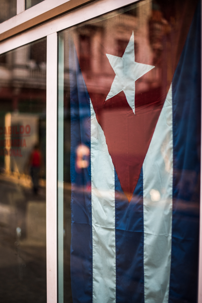 The Cuban flag is proudly displayed in a shop window against the reflection of a Havana street.