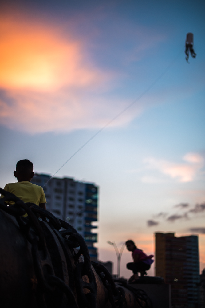 A boy flies his kite while sitting atop a massive cannon once belonging to the USS Maine.  The momunet to the Maine sits along the Malecon on the northern edge of Havana.