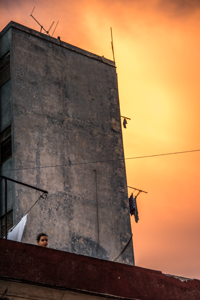 A young girl looks over the ledge of her apartment's roof.  The setting sun lights the sky behind.