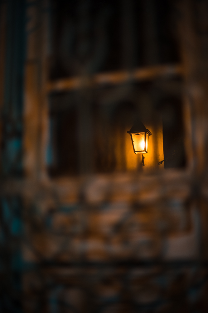 A street lamp reflects in a gated window.