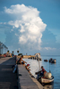 A thunderhead hovers over the Florida straight as a group of fisherman  bring their boat to dock for the morning.