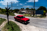 A bright red Russian Lata stops at a railroad crossing in the Cuban countryside.