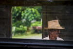 A Cuban man in a brilliant straw hat waits at a railroad stop.