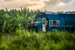 Four men hang out on an abandoned locomotive in rural Cuba.