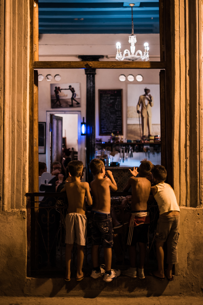 A group of Cuban boys say hello to a couple tourists through the windown of a restaurant.