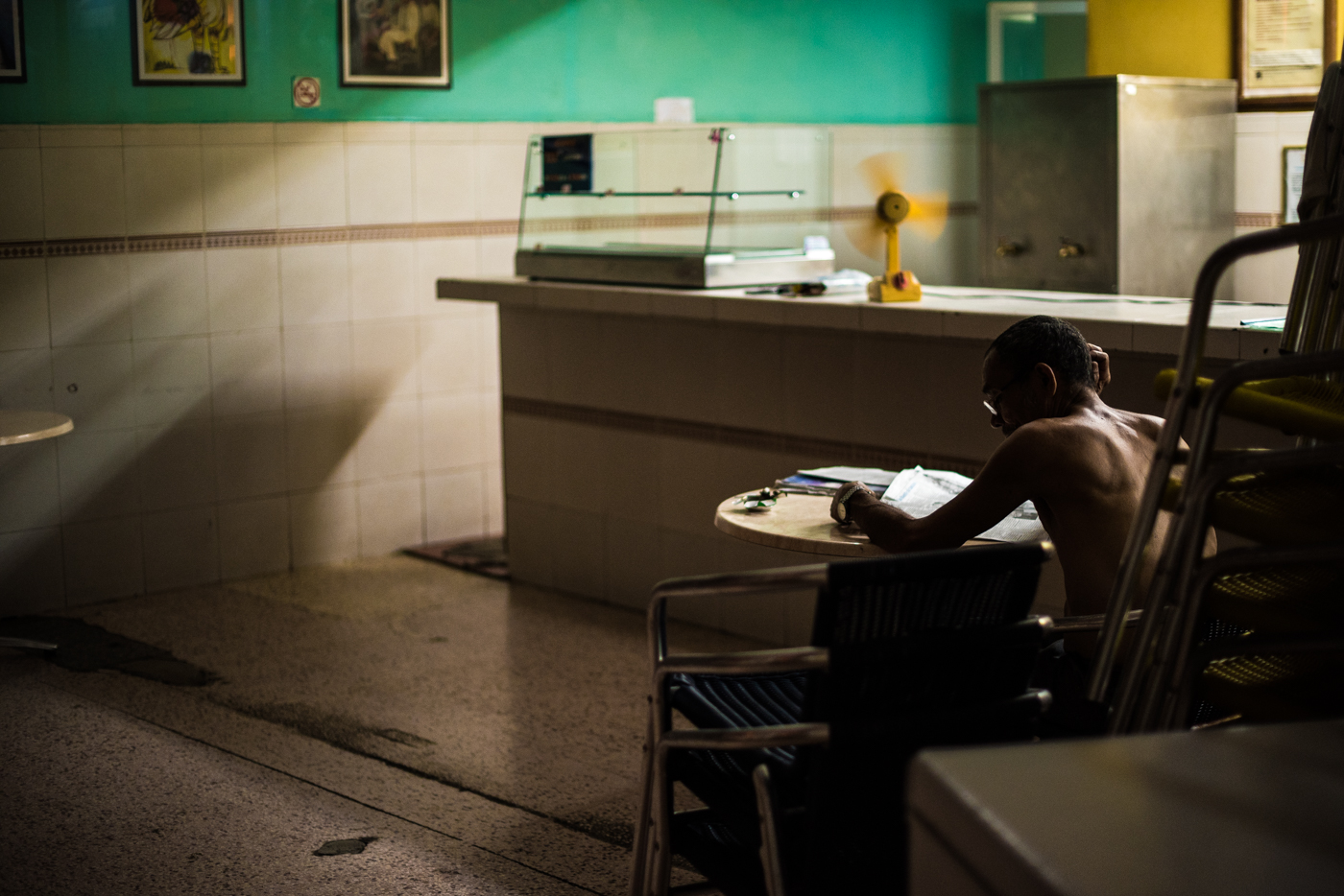 A man cools off in his diner after he has closed up shop.  It's a perfect time for the news.