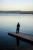 A man stands on a concrete dock observing the glassy surface of a lake.