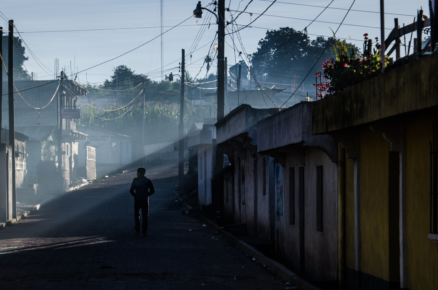 A man walks through the haze of early morning cookfires in San Pablo.