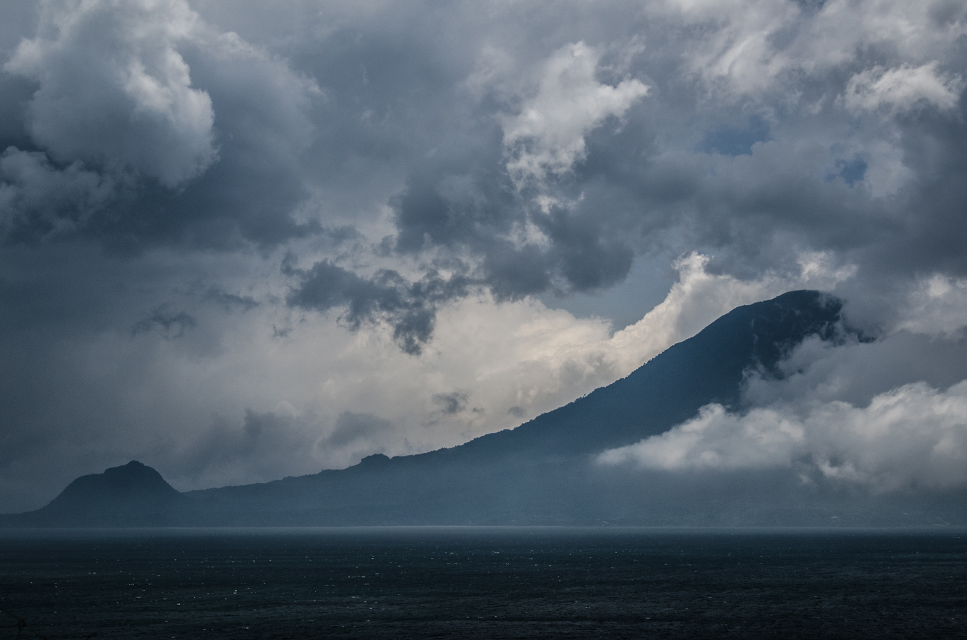 Clouds shroud Volcan Tolimán as a late afternoon storm forms over the lake.