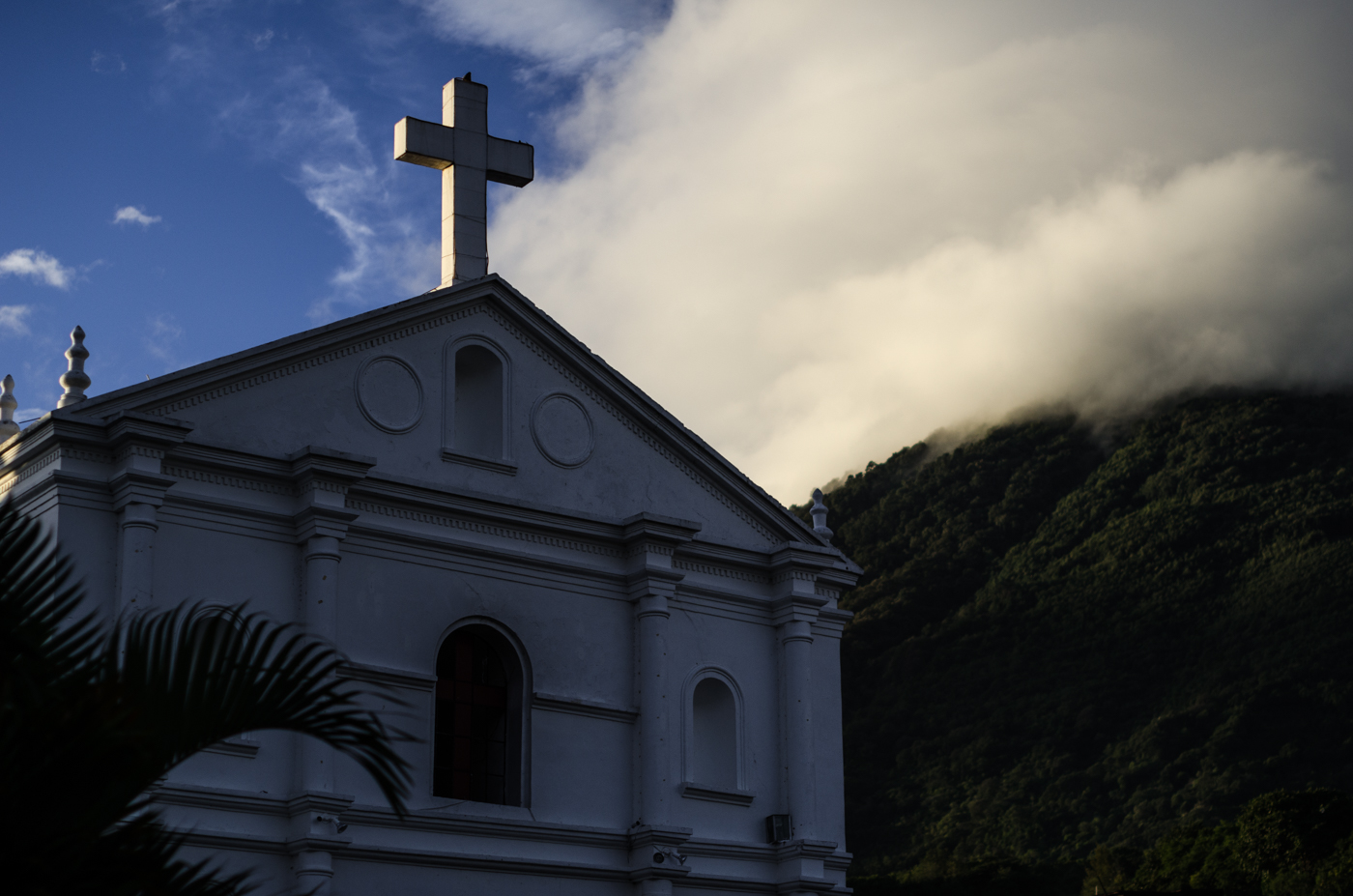 Clouds spill over the side of the mountain towards the Catholic Church of San Pedro.