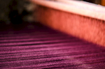 Taught purple threads on the backside of the loom feed through the orange and are then woven perpendicularly.