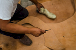 Leonel sizes a piece of leather to use as a sole.