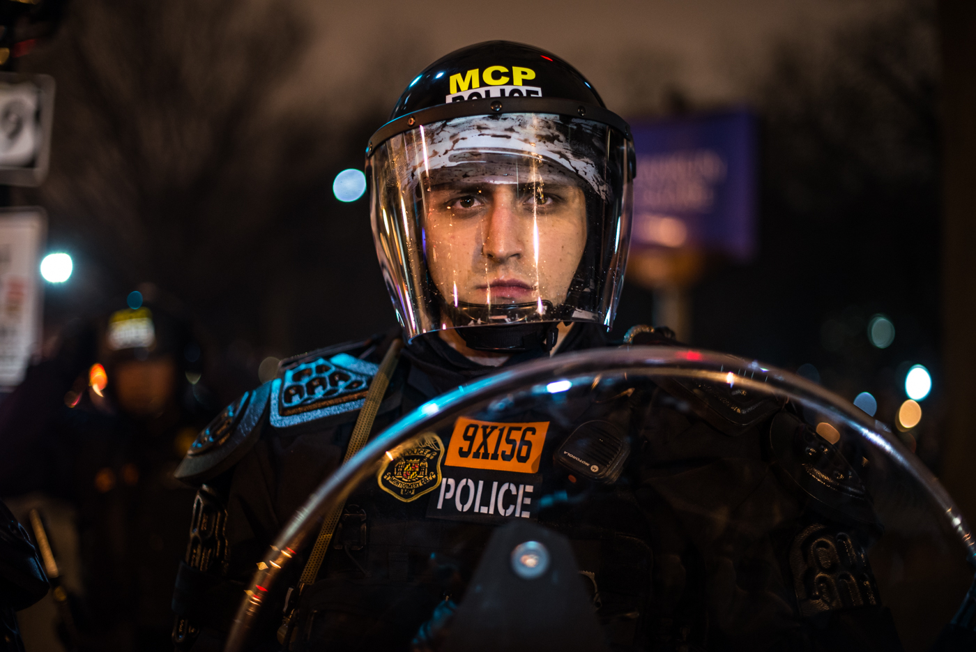 An officer stands behind his clear riot shield on Inauguration night.
