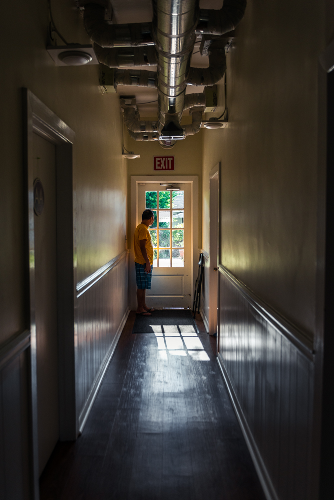 Durham, North Carolina, 2018Samuel stares out of the door of the basement where he had been living. Right outside people and vehicles fly by on the busy street.