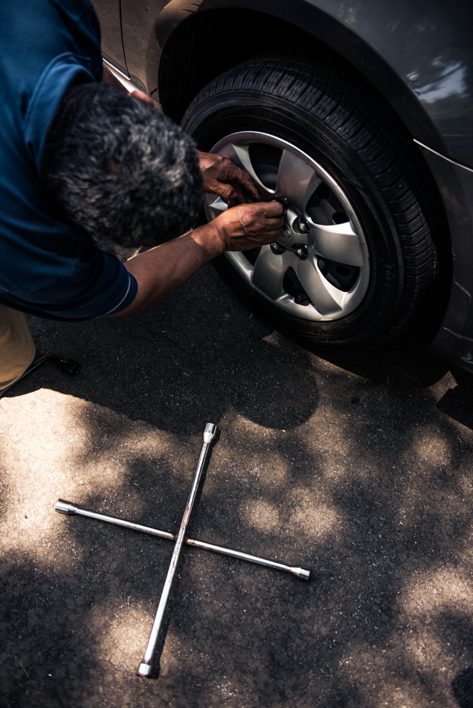 Durham, North Carolina, 2018A hubcap is replaced after the wheels of a church member's car have been painted. Tasks like these pass time and come with a bit of pay.