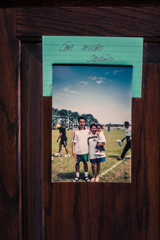 "Durham, North Carolina, 2018An image on a cabinet, captioned ""with much affection"", reminds Samuel of a better time in the United States. He stands on a soccer field with his family in Greenville, North Carolina."