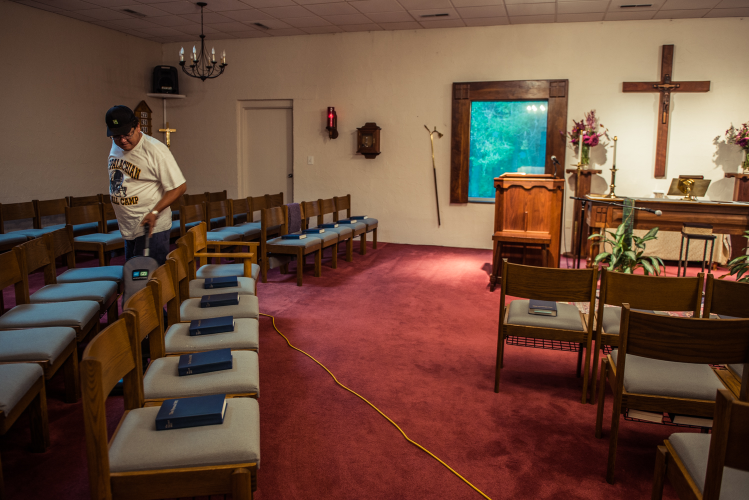 Greensboro, North Carolina, 2018Juana's husband vacuums on a Saturday evening  They help to ready the church for Sunday mass every week.