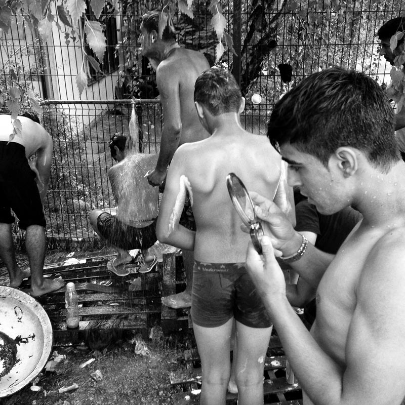 july 27, 2015. refugees wait in line to take a shower under a cold water tap, subotica, serbia.