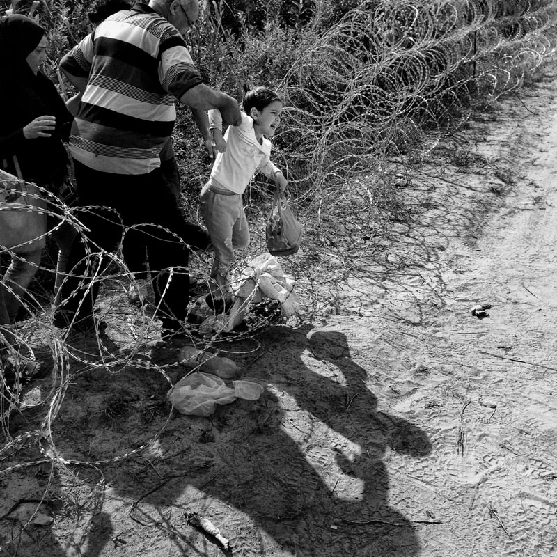 Sept. 3, 2015. A man helps a child as they jump over a section of the fence along the Serbian-Hungarian border, Roszke, Hungary.