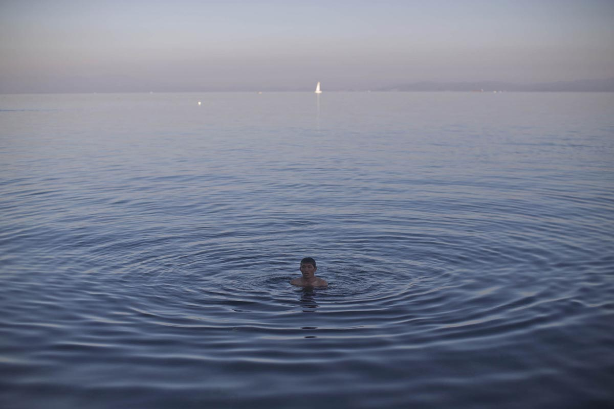 An Afghan refugee takes a swim in the Aegean, Lesbos, Greece, Nov. 4, 2015.