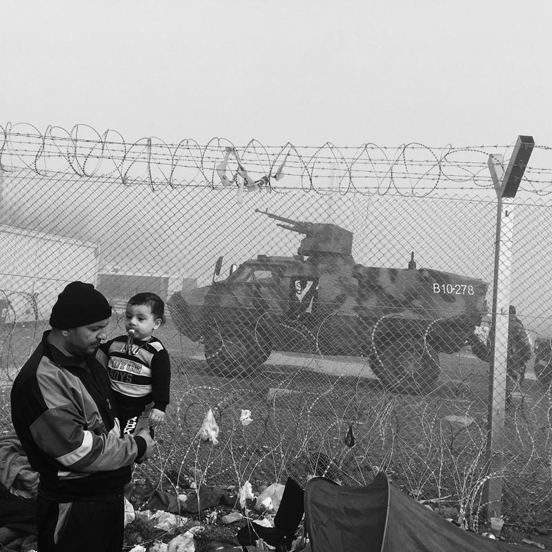 March 8, 2016. A man and his son stand next to a portion of the border fence between Greece and Macedonia, Idomeni refugee camp, Greece.