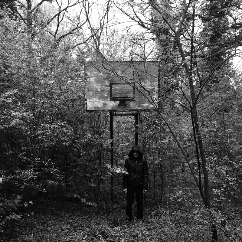 april 8, 2016. a refugee stands by a decrepit basketball hoop, principovac refugee camp, serbia.