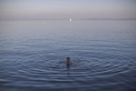 An Afghan refugee takes a swim in the Aegean, Lesbos, Greece, Nov. 4, 2015.