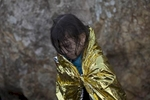 A child stands at a beach after arriving in a rubber boat from Turkey, Lesbos, Greece, Oct. 31, 2015.