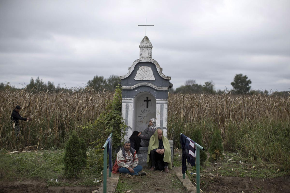 refugees rest by a roadside chapel, strosinci, croatia, sept. 26, 2015.