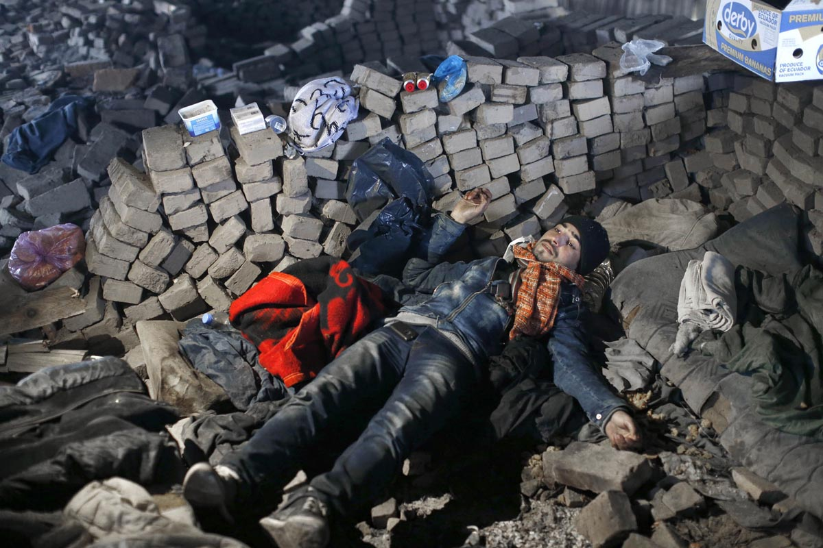 a refugee rests at an abandoned brick factory, outskirts of subotica, serbia, dec. 15, 2014.