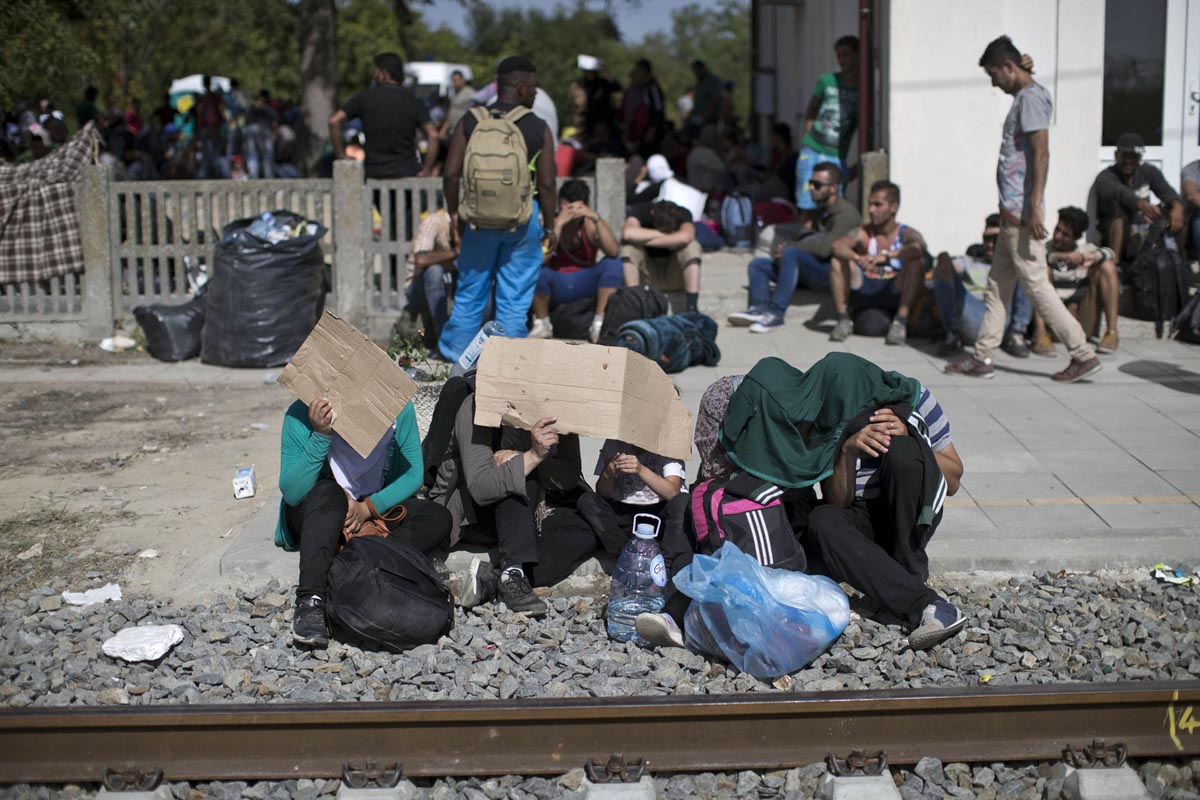 a family cover themselves from the harsh sun as they wait for a train, tovarnik, croatia, sept. 17, 2015.