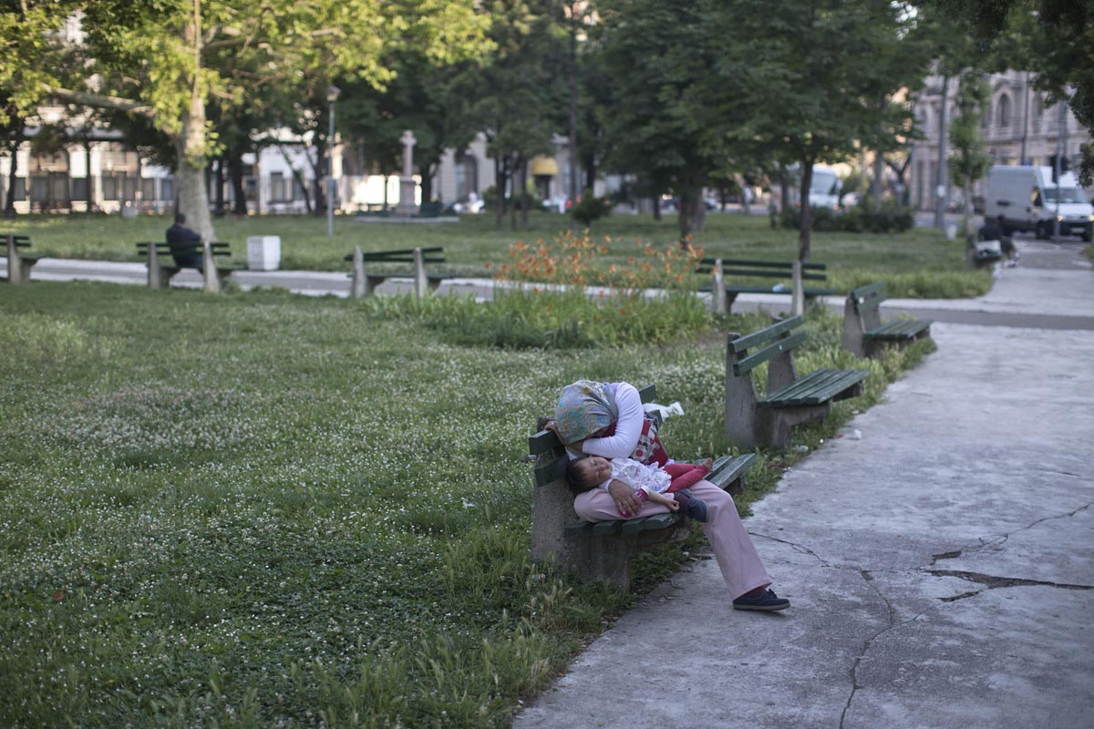 a refugee from afghanistan sleeps with her baby at a park, belgrade, serbia, june 12, 2015.